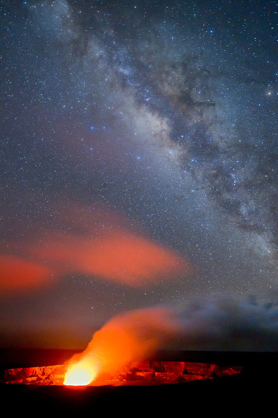 Glowing gases rising from Halemaumau Crater in the center of Kilauea Caldera, illuminates evening fog layer with the Milky Way in the sky above.  Hawaii Volcanoes National Park, Hawaii.