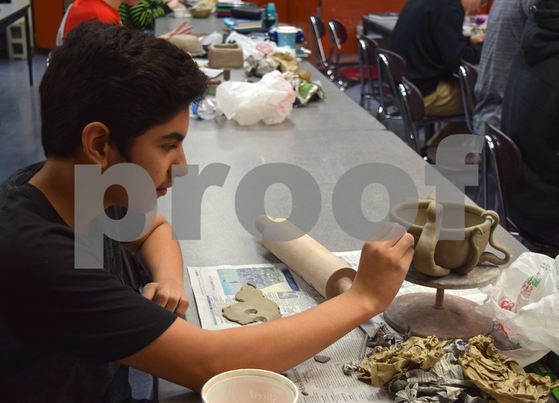 Sycamore High School freshman Heriberto Lopez adds eyes to his bowl designed to look like an octopus during art class on Feb. 24. Lopez's bowl and other bowls created by Sycamore High School students and faculty will be sold during an event on April 19 to raise money for the Sycamore Food Pantry.