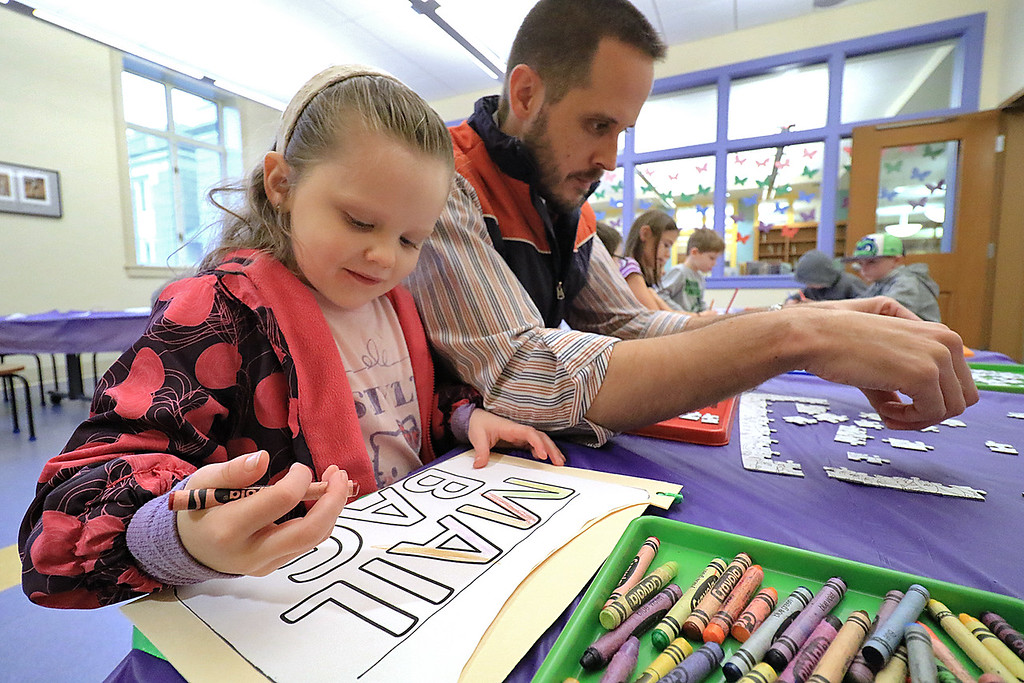 . Emilia Krans, 4, colors a paper mail bag she made during craft time at the Leominster library on Friday morning, December 29, 2018 as her dad puts together a color-me puzzle. SENTINEL & ENTERPRISE/JOHN LOVE