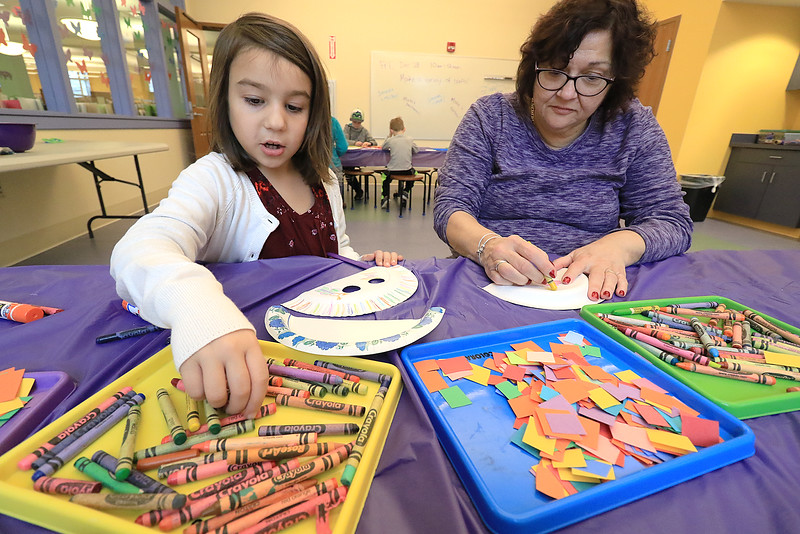 Sofia Bosse, 5, decorates a paper plate mask as her grandmother Fran Sullivan just decorates a paper plate during craft time at the Leominster library on Friday morning, December 29, 2018. SENTINEL & ENTERPRISE/JOHN LOVE