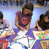 William Krans, 6, and his sisters Lydia Krans, 10 and Rebekah Krans, 8, color paper mail bags they made during craft time at the Leominster library on Friday morning, December 29, 2018.  SENTINEL & ENTERPRISE/JOHN LOVE