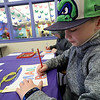 Caleb Conchieri, 9, colors a paper mail bag he made during craft time at the Leominster library on Friday morning, December 29, 2018. SENTINEL & ENTERPRISE/JOHN LOVE