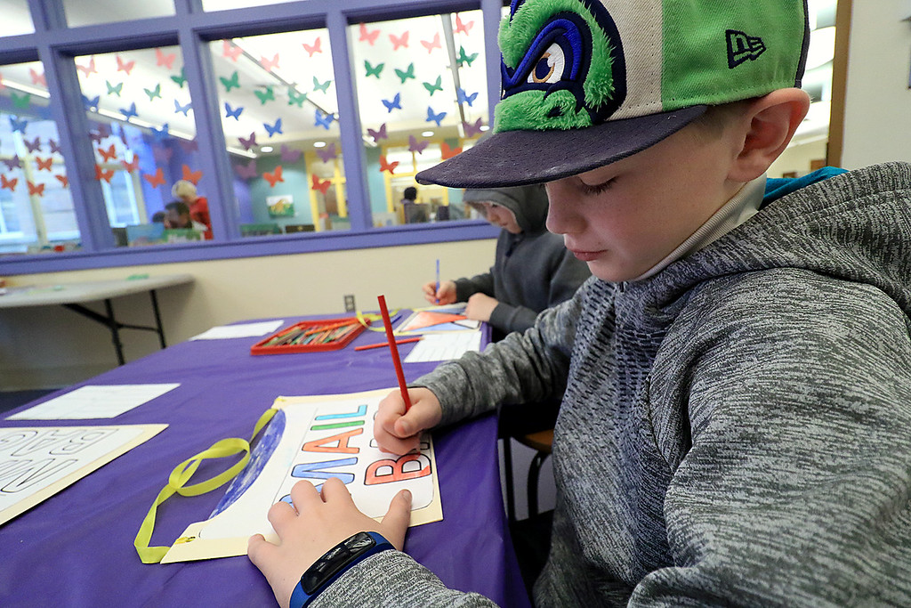 . Caleb Conchieri, 9, colors a paper mail bag he made during craft time at the Leominster library on Friday morning, December 29, 2018. SENTINEL & ENTERPRISE/JOHN LOVE