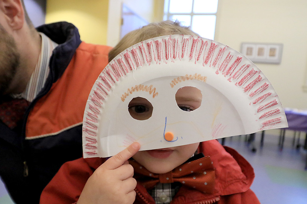 . Isaiah Krans, 2, show off the paper plate mask he made and decorated during craft time at the Leominster library on Friday morning, December 29, 2018. SENTINEL & ENTERPRISE/JOHN LOVE
