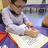 William Krans, 6, colors a paper mail bag he made during craft time at the Leominster library on Friday morning, December 29, 2018. SENTINEL & ENTERPRISE/JOHN LOVE