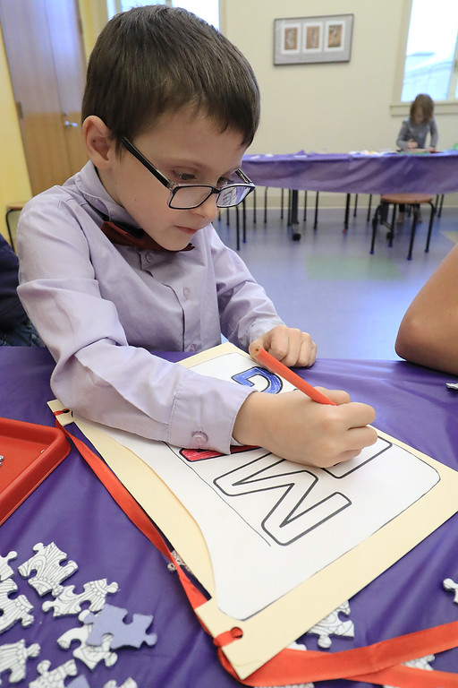 . William Krans, 6, colors a paper mail bag he made during craft time at the Leominster library on Friday morning, December 29, 2018. SENTINEL & ENTERPRISE/JOHN LOVE