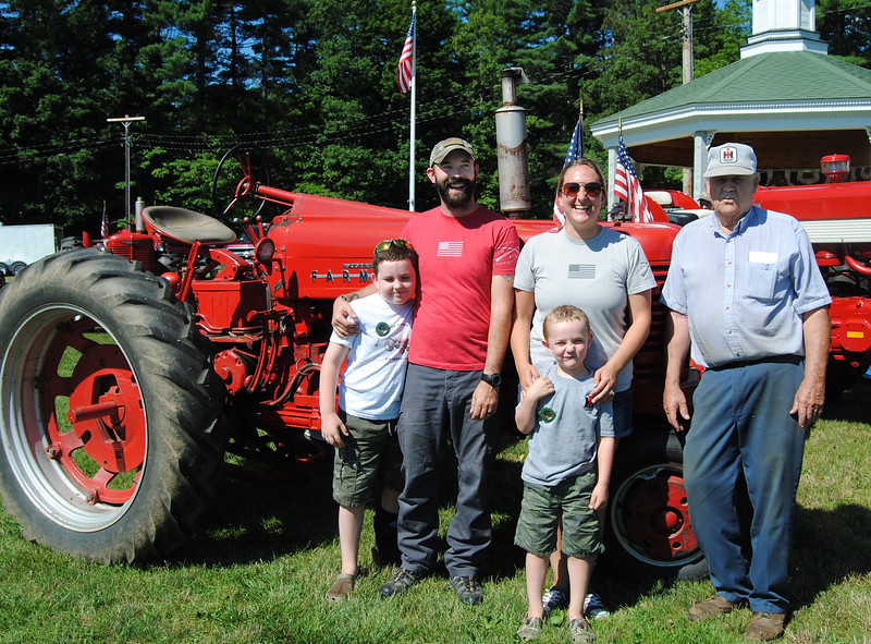NASHOBA VALLEY VOICE/ANNE O'CONNOR<br /> Crank Up, a show with engines, tractors and much else, has been in Pepperell every summer since 1975. Kim Spaulding, left, was one of the founders. His granddaughter and her husband, Christine and Joshua Thompson, organize the event that draws aficionados from New England and New York. The Thompson's sons, Michael on left and Nathan, really want to drive that big, red tractor.