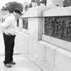 Veteran of all 3 wars, Burton M., stops to examine the brass sculptures along the walls of the WWII memorial