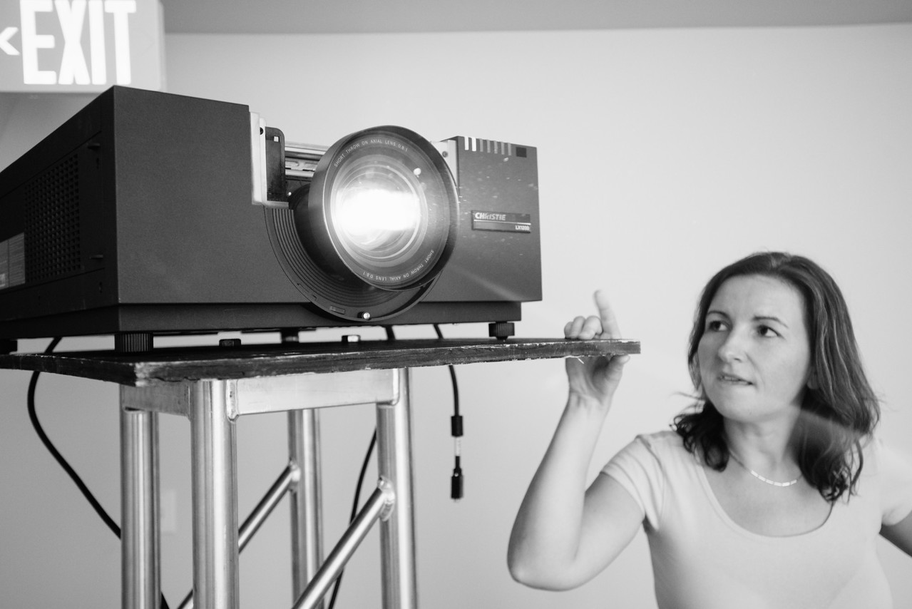 1 day until launch. We test out our 15,000-lumen super-bright projector rental for tomorrow's launch, and it looks awful. Plan B in motion. Pictured: Customer Support Manager Ana Pogacar.
