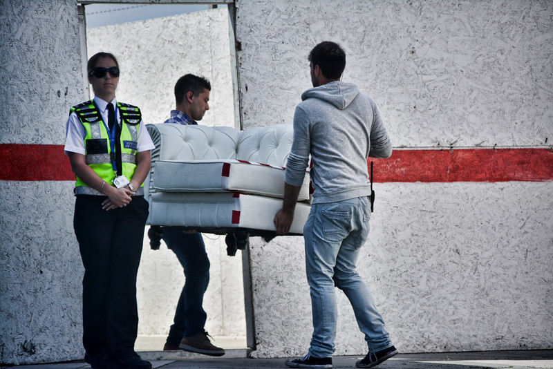 Men carrying a sofa with security guard next to them