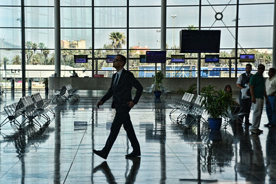 Man in black suit walk through the international airport terminal