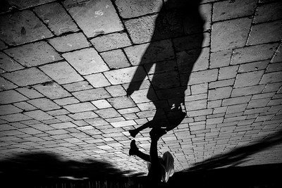Shadow of a child riding a scooter on a stone paved plaza
