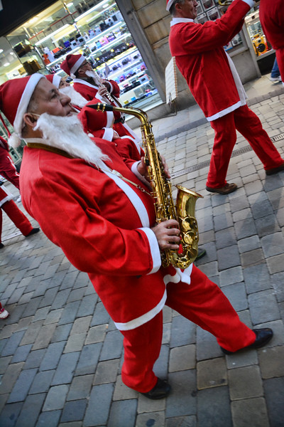 Gibraltar - 5th December 2014 - Gibraltar today saw a long line of Santas gather at Casemates before heading into Main Street in a Conga dance. Evening shoppers were treated to the Santa conga dance as they headed to the Piazza before turning back again to Casemates. The event was part of a charity run organised by the Rotary Club, and assisted by teh Calpe band. All images are available for purchase as prints at http://corephotographygibraltar.com/gallery/Santas-do-the-Conga-dance-through-Main-Street/G0000sqDL7SD0rwQ/C0000QCG2Y4bC50c