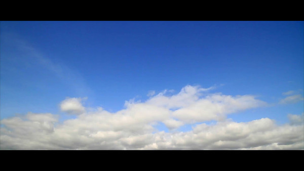 A time-lapse video of blue sky and white fluffy rolling clouds going left to right.