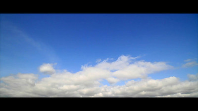 "File name: ""Sky Time Lapse 60FPS"" A time-lapse video of blue sky and white fluffy rolling clouds going left to right."