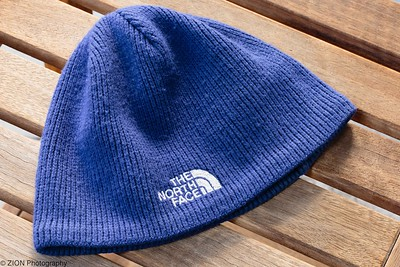 A North Face beanie on a side table