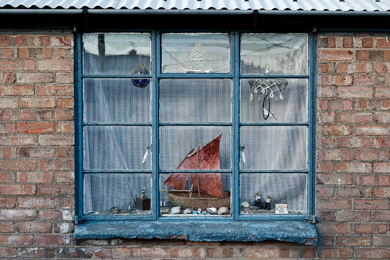 Digitally altered photo of a window in chandler's shop, Wells next the Sea, Norfolk.  Posterized and de-saturated