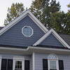 "Added an "" A "" frame over the main gable roof.<br /> <br /> ""Straight shake style Hardie plank siding""   Introducing an accent color really brings the architectural change out.  Water tables were extended and dressed with Black metal roofing."