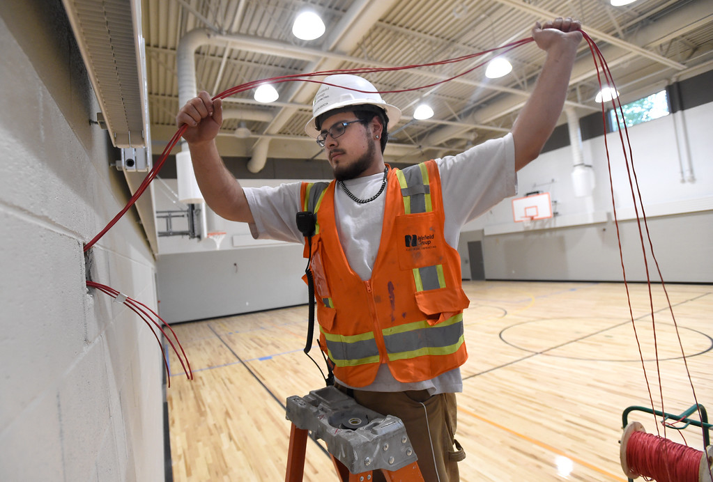 . Electrician Brandon Garcia, with Weifield Group Contracting, feeds wire into the wall of the gymnasium as he works to install a fire alarm while doing construction at Creekside Elementary School on Tuesday in Boulder. For more photos of the construction go to www.dailycamera.com Jeremy Papasso/ Staff Photographer/ May 16, 2017