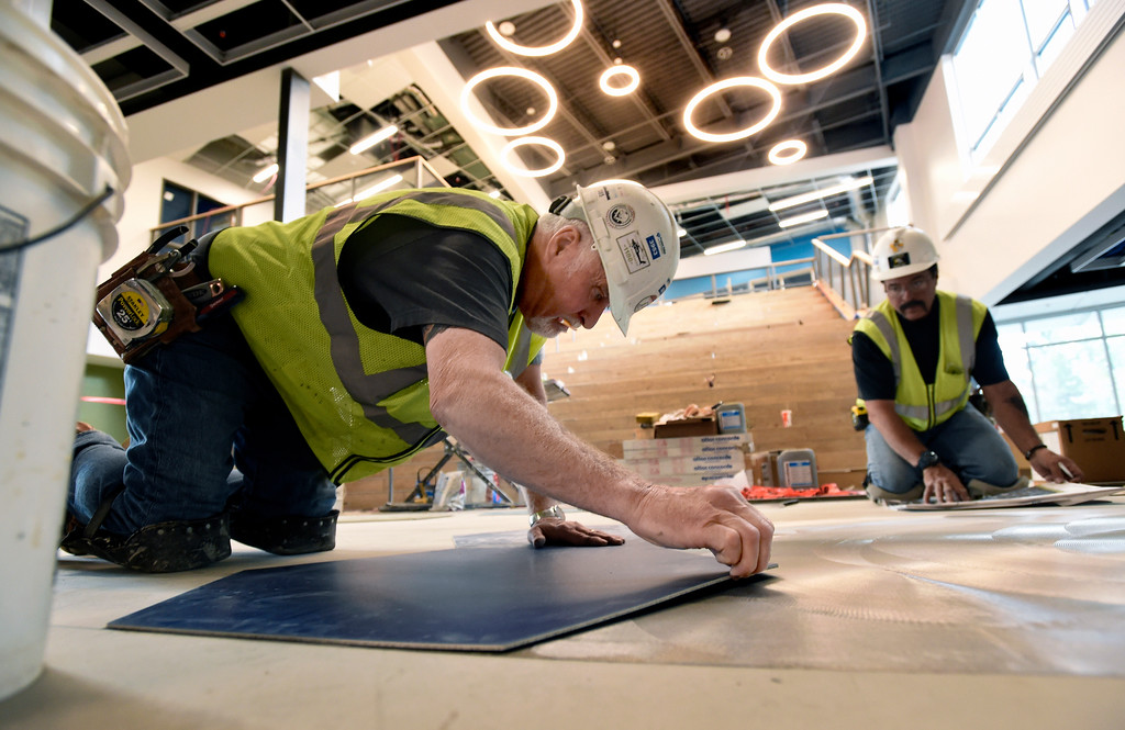 . Steve Guerin, left, and Mike Shaw, both with Next Generation Surfaces, install floor tiles in the main gathering area while doing construction at Creekside Elementary School on Tuesday in Boulder. For more photos of the construction go to www.dailycamera.com Jeremy Papasso/ Staff Photographer/ May 16, 2017