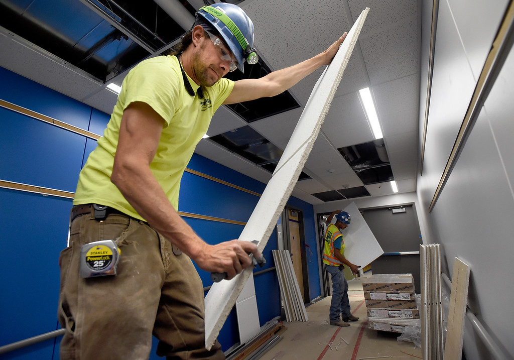 . Steven Snyder, at left, and Israel Martinez, both with Heartland Acoustics and Interiors, work to install ceiling tiles while doing construction at Creekside Elementary School on Tuesday in Boulder. For more photos of the construction go to www.dailycamera.com Jeremy Papasso/ Staff Photographer/ May 16, 2017