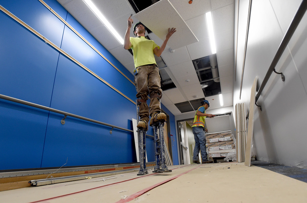. Steven Snyder, left, and Israel Martinez, both with Heartland Acoustics and Interiors, work to install ceiling tiles while doing construction at Creekside Elementary School on Tuesday in Boulder. For more photos of the construction go to www.dailycamera.com Jeremy Papasso/ Staff Photographer/ May 16, 2017