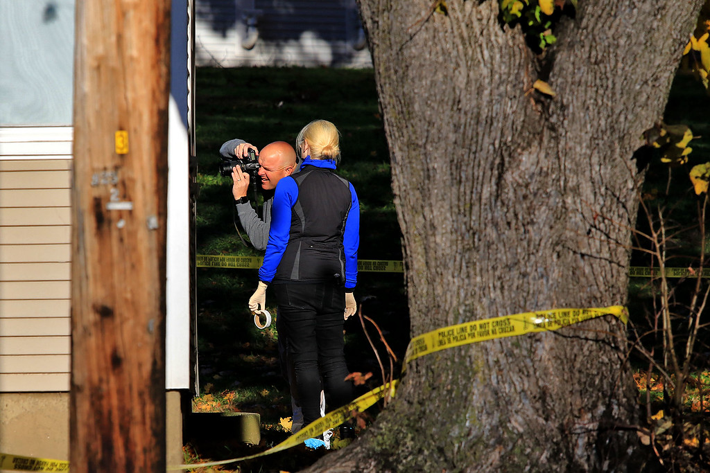 . An investigators takes pictures in the yard of the crime scene at 35 Wanoosnoc Road in Fitchburg on Wednesday morning, November 7, 2018. SENTINEL & ENTERPRISE/JOHN LOVE