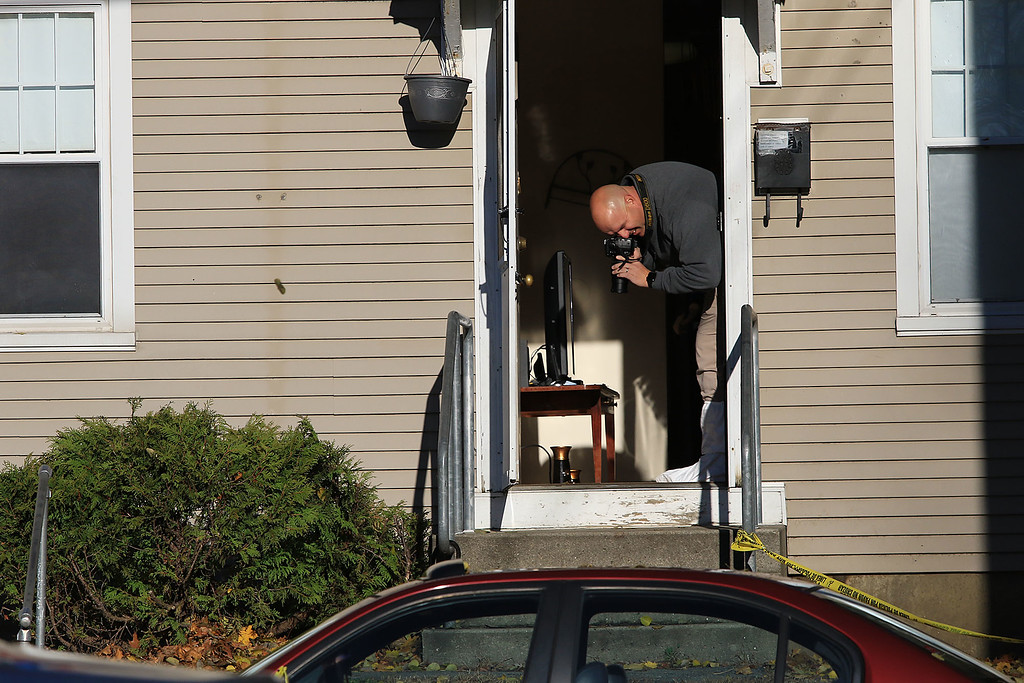 . An investigators takes pictures in the doorway of the crime scene at 35 Wanoosnoc Road in Fitchburg on Wednesday morning, November 7, 2018. SENTINEL & ENTERPRISE/JOHN LOVE