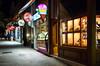 Shops along a street in Opatija, Croatia at night.