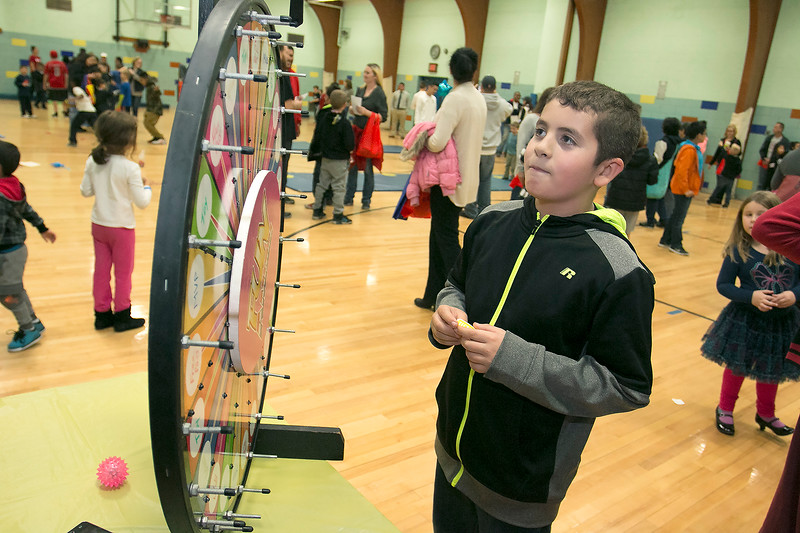 """Crocker Elementary School hosted its first annual """"Fuel Up to Play 60"""" Health Fair on Thursday night at the school. Fourth grader Jack Kirrane, 9, spins the whell at the Roll on America booth at the event to try and win a prize. SENTINEL & ENTERPRISE /JOHN LOVE"""