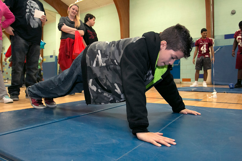 """Crocker Elementary School hosted its first annual """"Fuel Up to Play 60"""" Health Fair on Thursday night at the school. Fifth grader Malachi Herbert, 11, does some pushups at one of the health stations in the gym at the event. SENTINEL & ENTERPRISE /JOHN LOVE"""