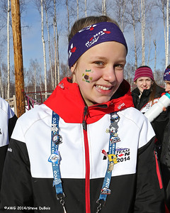 A female racer in xc freestyle shows off her pins at the awards ceremony.