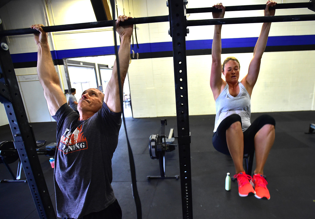 . Todd Roadman, left, and Elise Reinhard work on the bars doing toes to bar exercises during class at CrossFit Lefthand in Boulder on Tuesday. For more photos go to dailycamera.com. Paul Aiken / Staff Photographer July 3, 2018