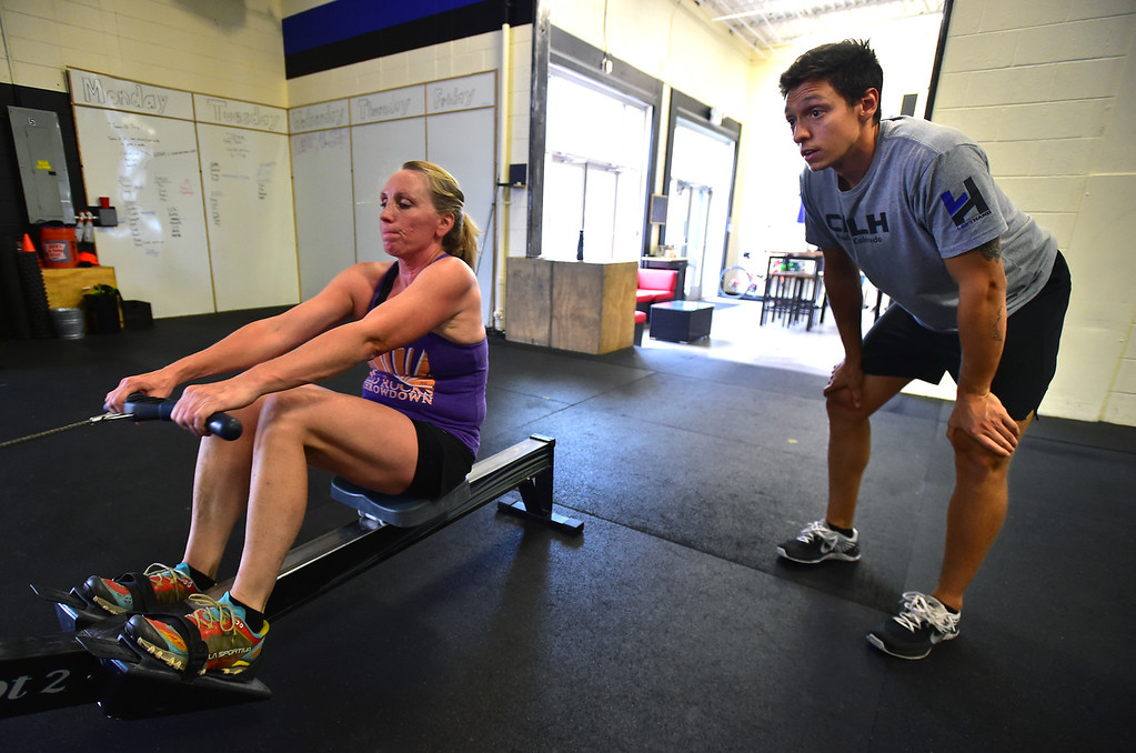 . Mary Rios gets encouragement from instructor Patrick Rios, as she works on the rowing machine during class at CrossFit Lefthand in Boulder on Tuesday. For more photos go to dailycamera.com. Paul Aiken / Staff Photographer July 3, 2018