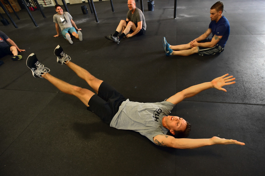 . Instructor Patrick Rios demonstrates a warmup exercise during class at CrossFit Lefthand in Boulder on Tuesday. For more photos go to dailycamera.com. Paul Aiken / Staff Photographer July 3, 2018