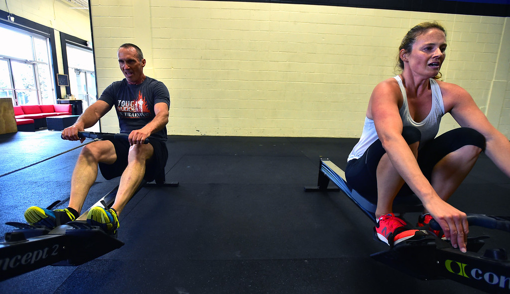 . Todd Roadman, left, and Elise Reinhard work on the rowing machines during class at CrossFit Lefthand in Boulder on Tuesday. For more photos go to dailycamera.com. Paul Aiken / Staff Photographer July 3, 2018