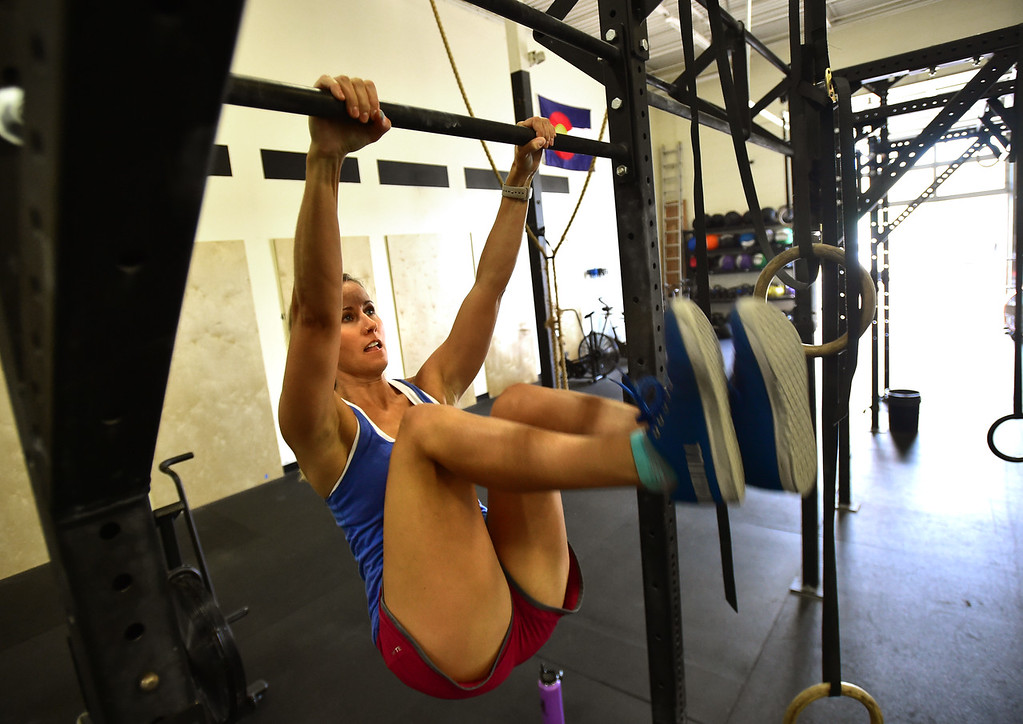 . Megan Saad performs a toes to bar exercise during class at CrossFit Lefthand in Boulder on Tuesday. For more photos go to dailycamera.com. Paul Aiken / Staff Photographer July 3, 2018
