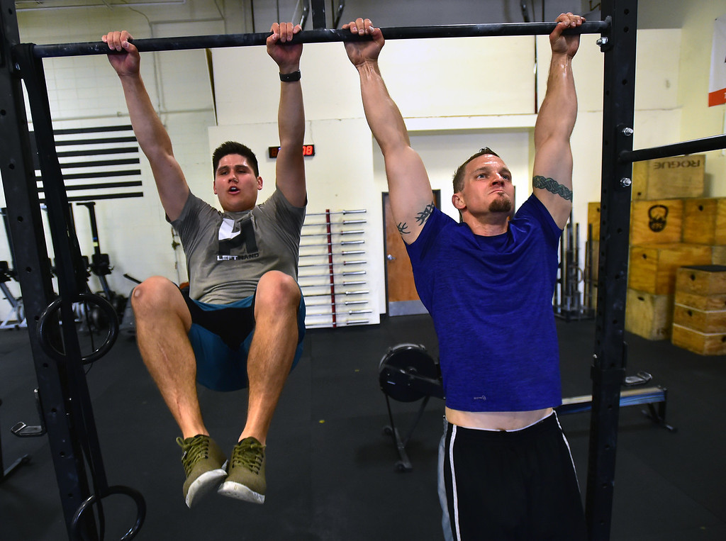 . Emmett Elizondo, left, and Jame Montague perform toes to bar during class at CrossFit Lefthand in Boulder on Tuesday. For more photos go to dailycamera.com. Paul Aiken / Staff Photographer July 3, 2018
