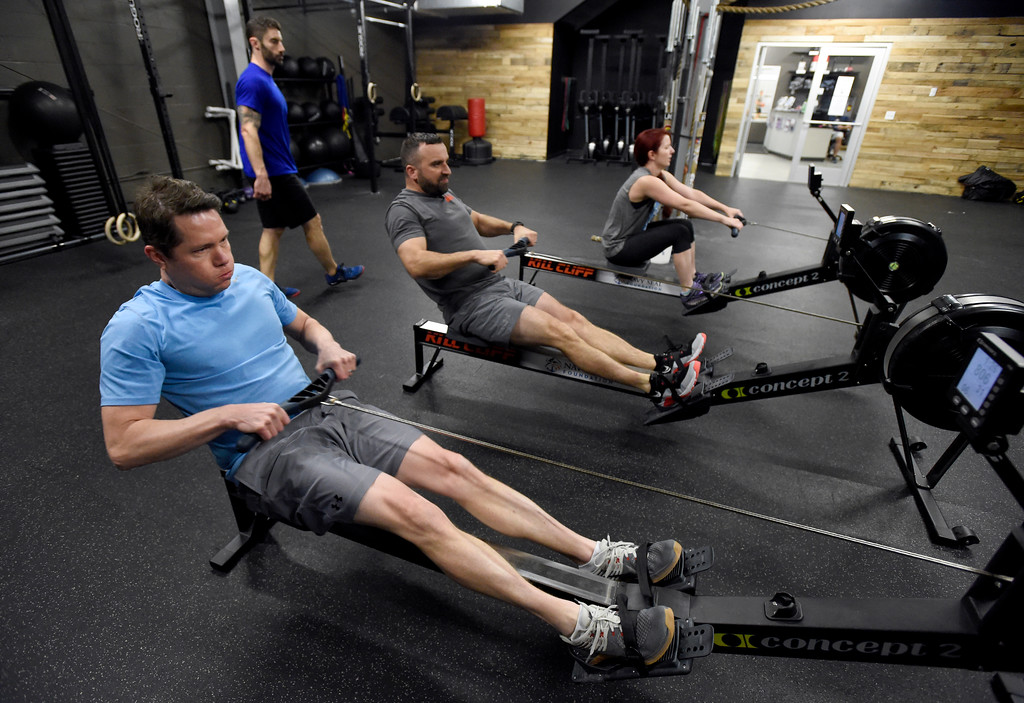 . Joshua Scott, left, uses a rowing machine during a Crossfit workout class at Impact Sports Performance on Thursday inside the Sports Stable in Superior. For more photos of the class go to dailycamera.com Jeremy Papasso/ Staff Photographer 12/28/2017