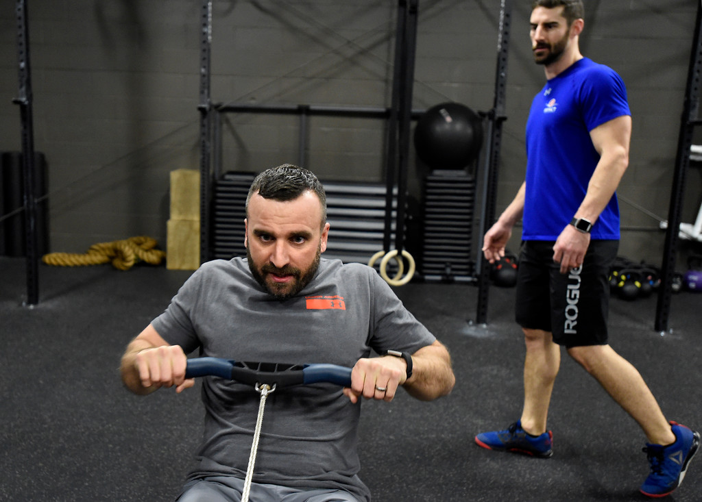 . John Schminky, left, uses a rowing machine during a Crossfit workout class at Impact Sports Performance on Thursday inside the Sports Stable in Superior. For more photos of the class go to dailycamera.com Jeremy Papasso/ Staff Photographer 12/28/2017