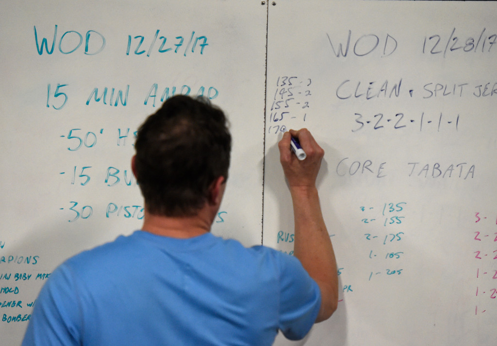 . Joshua Scott writes down results from his exercise during a Crossfit workout class at Impact Sports Performance on Thursday inside the Sports Stable in Superior. For more photos of the class go to dailycamera.com Jeremy Papasso/ Staff Photographer 12/28/2017