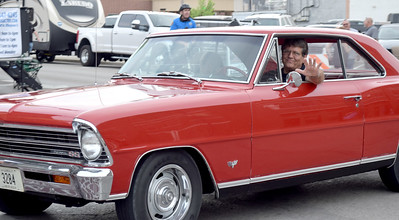 A car enthusiast waves as he drives the route during Cruise Night on Friday. Kaitlin Cordes photo