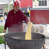 Jay Macklin of Mason pours popcorn kernels into a kettle during Crusie Night Friday. Macklin owns Macklin Meadow Kettle Corn. Kaitlin Cordes photo