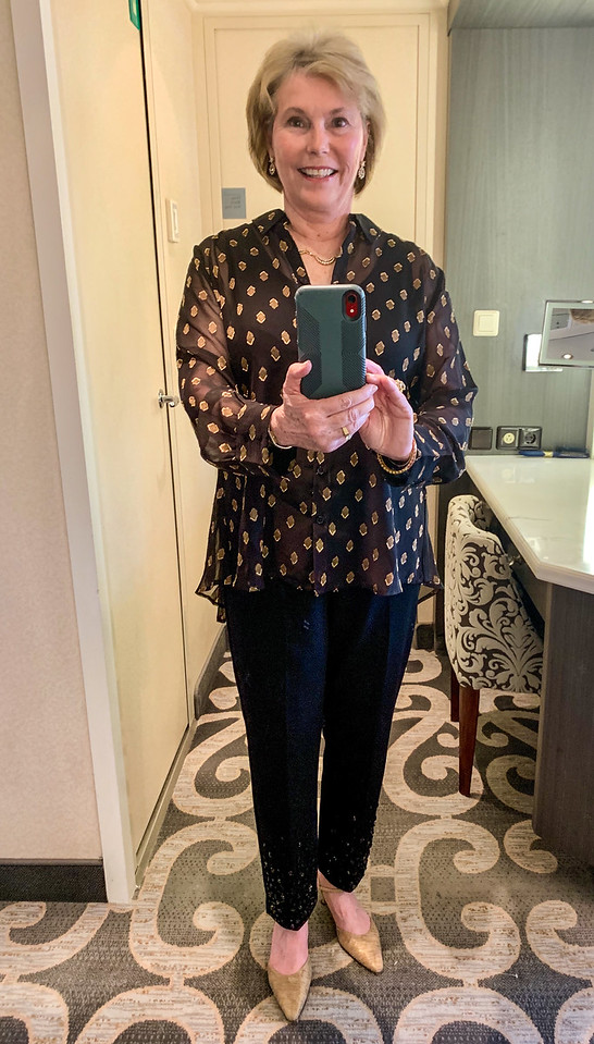 A boomer woman models an Alaska cruise formal night outfit consisting of black pants and gold and black top.