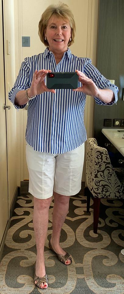 Boomer woman wearing Chico's blue stripe no-iron shirt and white Neema Ava shorts.
