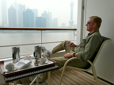 A man sits on the balcony of a cruise ship looking at the smoggy Shanghai skyline