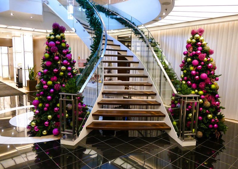 Two Christmas trees with purple and green ornaments by a ship's staircase