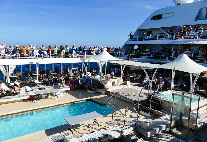 Passengers line the deck above the pool on a ship to see the Crossing the Equator ceremony.