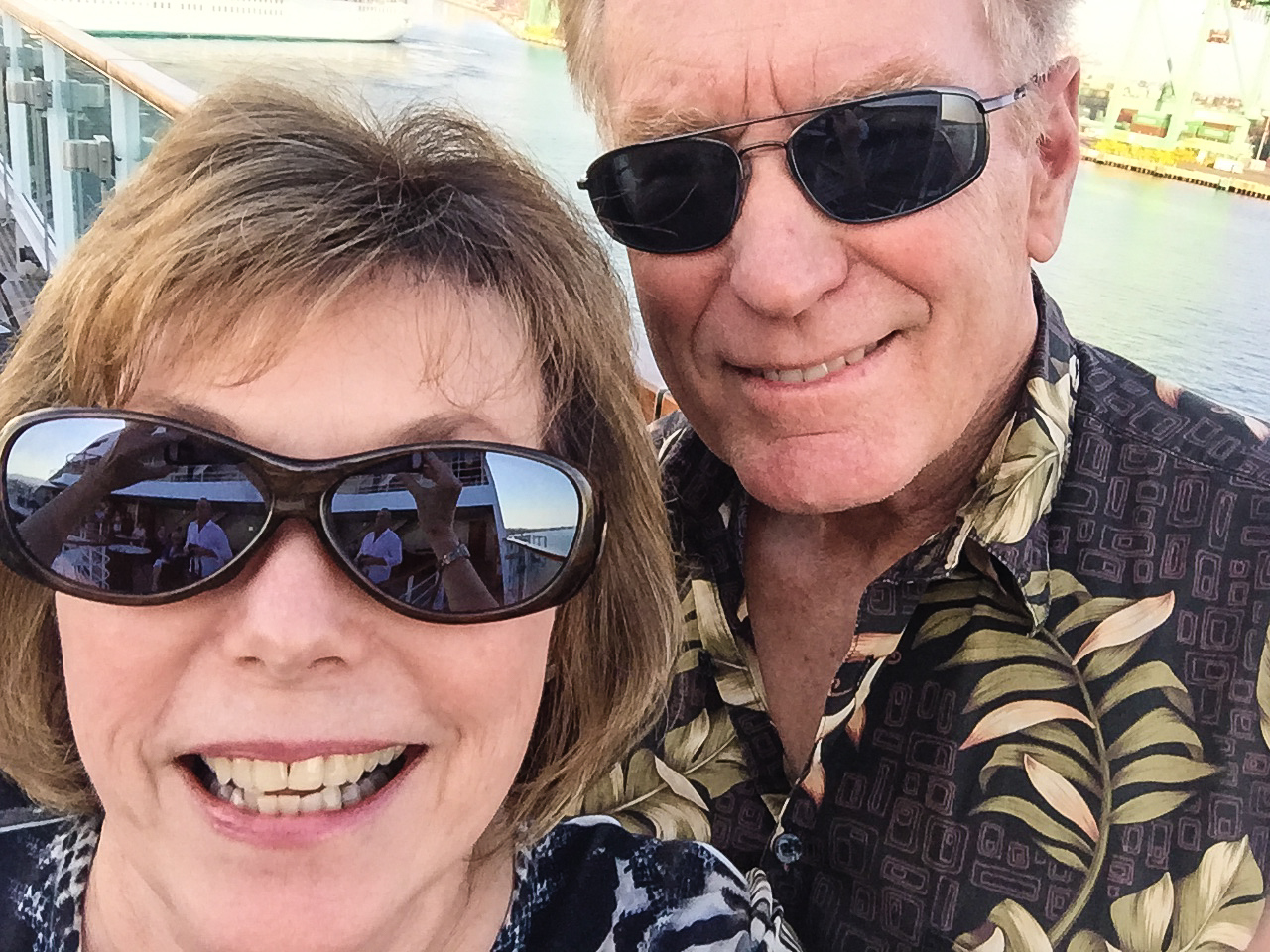 A baby boomer man and woman smile as they leave on a luxury cruise.
