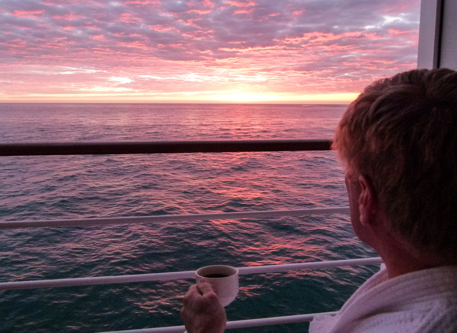 Boomer man holding a cup of coffee watching the sunrise from the veranda of a luxury ship.